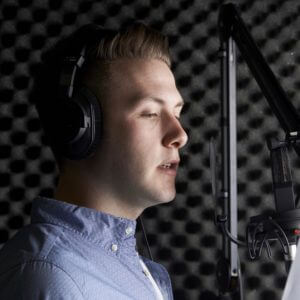 Man In Recording Studio Talking Into Microphone - Global Voice Acting Academy
